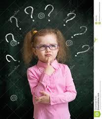Ребенок стоя близко доска школы с много вопросительных знаков