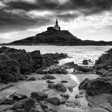 <b>Lighthouse landscape</b> with stormy sky over <b>sea</b> with rocks in fore ...