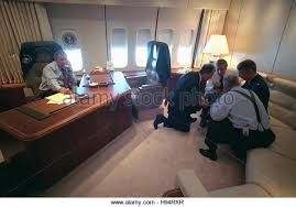us president george w bush talks on the phone as senior staff huddle in his air force 1 office