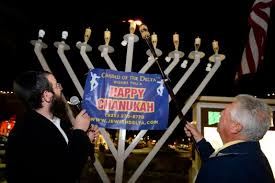 rabbi dovber berkowitz with the chabad of the delta watches as brentwood mayor robert taylor lights breaking lighting set
