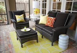 yellow black sunroom with black wicker furniture with black cushions white piping yellow graphic rug white modern garden stool with kenneth wingard blacks furniture