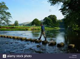 stepping stones man crossing stepping stones on the river hodder near whitewell in the