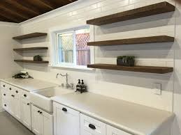 polished reclaimed wood wall shelves flanking floating  custom brown stained wooden floating kitchen shelves on whit