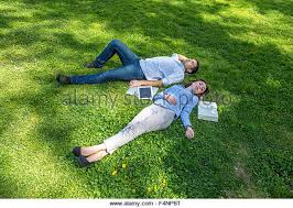 two people napping on grassy lawn stock image business nap office relieve