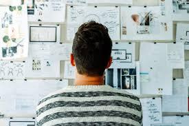 reasons enterprise companies need liberal arts graduates proto a photo of a man looking at a wall full of design ideas