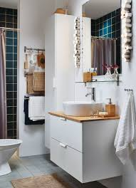 a small white bathroom with a high cabinet and a washstand combined with accessories in bamboo brown bathroom furniture