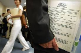 A man holds his buzzword heavy resume at a job fair The Cheat Sheet