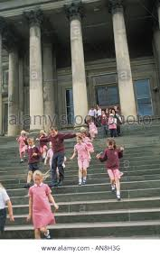 england style steps: school children run down steps at the liverpool museum in england stock image