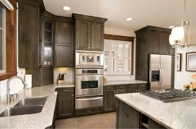 countertops dark wood kitchen islands table: dark wood cabinetry contrasts with white marble countertops in this kitchen featuring brushed aluminum appliances