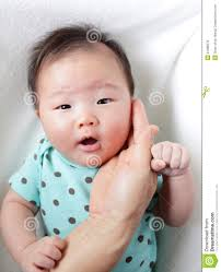Mother hand touch baby smile face, child are asian girl. MR: YES; PR: NO - mother-hand-touch-baby-smile-face-24398576