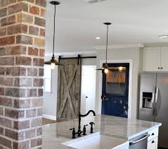 country kitchen column spout: country style kitchen with brick column beside marble topped island with farm sink paired with an oil rubbed bronze hook spout faucet below a pair of