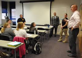 criminal justice program welcomes alumna agent fulton montgomery criminal justice professor paul giudilli standing far right asks follow up questions to