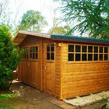 oak log cabins: corner view of a log cabin with double garage style doors and a single door in