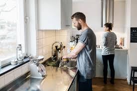 millennials the me me me generation time com man washing sauce pan while w standing in background in kitchen