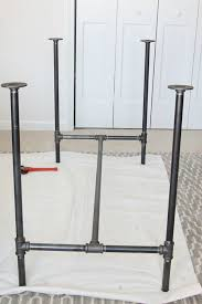 the assembled black pipe legs of a diy industrial chic workbench black iron pipe table