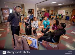 a local hispanic tattoo artist tells a group of multiracial a local hispanic tattoo artist tells a group of multiracial teenagers a success story about his business on a careers day at a community center in anaheim