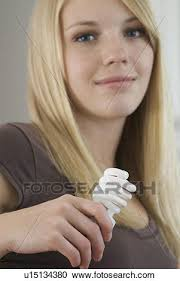 <b>Young woman</b> holding compact <b>fluorescent</b> bulb in kitchen, Brandon ...