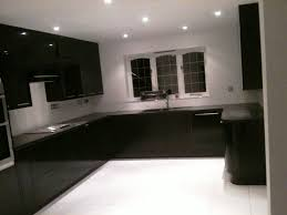 corian kitchen top: black corian vs granite countertop with dark wood cabinets and wooden floor plus recessed ceiling lighting