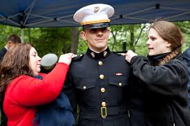 file u s marine 2nd lt christopher v posadas center stands as center stands as his mother left and his fiance pin second lieutenant bars on his uniform after graduating from the united states military academy at