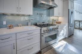 white beach house kitchen with linear glass backsplash tiles beach house kitchen nickel oversized pendant