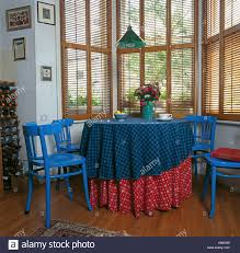 bright blue painted chairs at table with red and blue cloths in front of dining room bright painted furniture