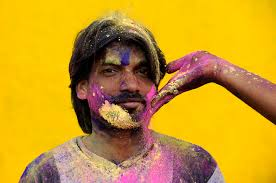 A man poses for a photograph while his friend wipes his cheek in colored powder before a Cricket World Cup match between India and the West Indies in ... - bp27