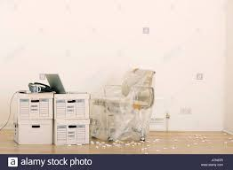 office chair wrapped in plastic sheet beside laptop on stack of file boxes in empty office boxes stack office file