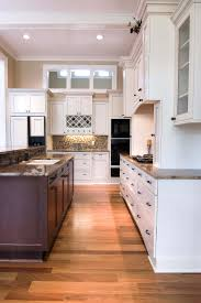 kitchen moldings: dark wood island stands apart in this kitchen flush with white painted cabinetry and moldings