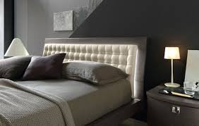 view in gallery gentle back light illuminates this slanting tufted headboard for a semi minimalist bedroom bedroom headboard lighting