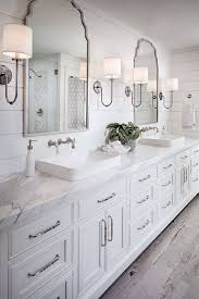 white bathroom floor: shiplap bathroom wall with white cabinetry white marble countertop wall mount faucet and rustic looking floor tile