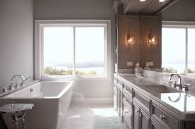 bathroom features gray shaker vanity: stunning grey bathroom features grey walls framing a modern freestanding tub paired with a deck mount tub filler situated beside window with stunning view