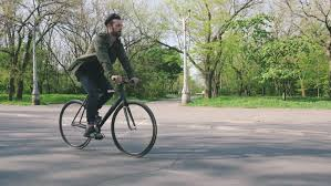 Tracking shot of <b>hipster</b> man riding <b>fixed gear</b> bicycle in park