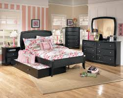 black polished teak wood bed frame with trundle on cream lacquer hardwood floor combined with mirror built in study furniture