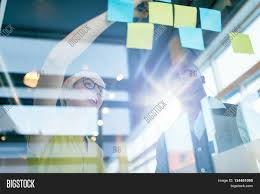 team of young casual business people collaborating on an creative planning project using a blue and bright modern office space