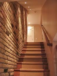 love the brick wall lighting and runner on the basement stairs by nessa basement stairwell lighting