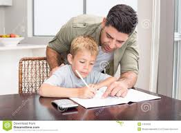 happy father helping son math homework at table stock happy father helping son math homework at table