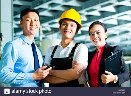 chinese shift supervisor or foreman together the owner or chinese shift supervisor or foreman together the owner or ceo and the manager standing proud in a factory
