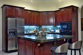 countertops dark wood kitchen islands table: a small eat in kitchen with rich cherry wood cabinets and stainless steel appliances
