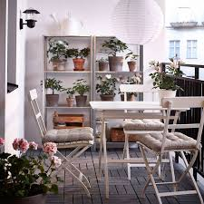 a balcony with white folding chairs and table together with shelving units in galvanised steel balcony furnished small foldable