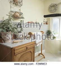 washstand bathroom pine:  green plants in pots on marble topped washstand in cottage bathroom with an old pine towel