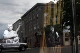 in greenfield a sense of uncertainty accompanies growing optimism the window of matt kim s academy of rock reflects a downtown streetscape of greenfield