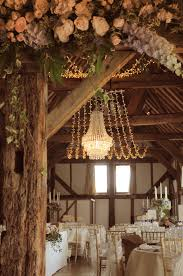 crystal chandelier with a fairy light canopy at the beautiful loseley park tithe barn beautiful lighting uk