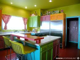bright colorful with green wall color also red granite floor and kitchen islands also marble countertop bright colorful home