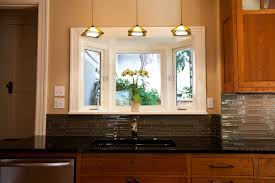 realy cool yelow and white over the sink kitchen lighting with dark glass tile backsplash and above sink lighting