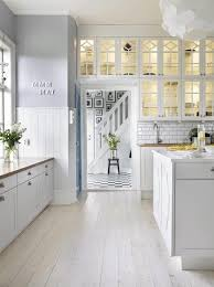 white kitchen windowed partition wall: pale lavender walls white kitchen cabinets white wood floors glass cabinet doors