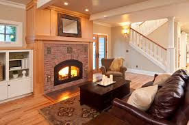a living room off of the foyer with a large wooden and brick mantle around the beautiful small livingroom