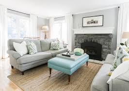 gray and blue living room features a pair of identical gray roll arm sofas lined with yellow and blue ikat pillows facing each other across from a turquoise blue gray living room