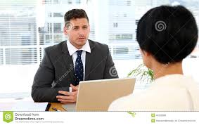serious doctor writing on clipboard while staff are standing businessman interviewing a w at his desk stock footage