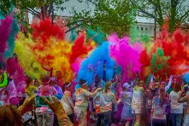 Runners throw dye at a color run