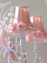 decidedly feminine chandelier white wrought iron and crystal beads fade into the background as pastel pink shades with silk rose trim take the spotlight background pink chandelier